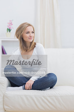 Casual thoughtful young woman sitting on sofa at home Stock Photo - Budget Royalty-Free, Image code: 400-06872338