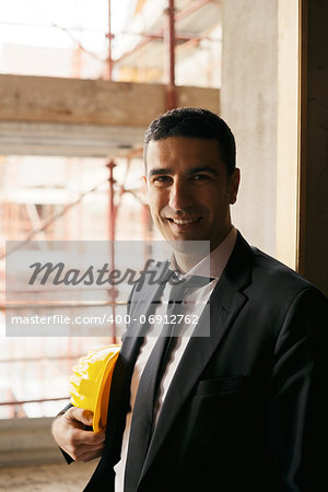 Professional people at work, portrait of happy and confident architect with safety helmet in construction site, smiling at camera Stock Photo - Budget Royalty-Free, Image code: 400-06912762