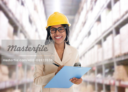 Smiling Indian woman doing stock tick in warehouse  with safety helmet smiling happy writing report. Portrait of beautiful Asian female model standing inside factory. Stock Photo - Budget Royalty-Free, Image code: 400-06922030