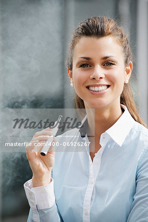 portrait of young female smoker smoking e-cigarette outdoor office building and looking at camera Stock Photo - Budget Royalty-Free, Image code: 400-06926267