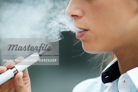 closeup of woman smoking e-cigarette and enjoying smoke. Copy space Stock Photo - Budget Royalty-Free, Image code: 400-06926269