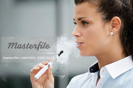 young female smoker smoking e-cigarette outdoors. Head and shoulders, side view Stock Photo - Budget Royalty-Free, Image code: 400-06928035
