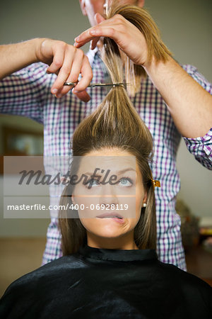 female client in hairdresser shop uncertain about cutting hair and biting lips Stock Photo - Budget Royalty-Free, Image code: 400-06928119