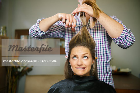 female client in hairdresser shop uncertain about cutting hair and biting lips Stock Photo - Budget Royalty-Free, Image code: 400-06928386