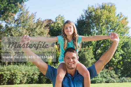Daughter sitting on dads shoulder and stretching her arms in the park Stock Photo - Budget Royalty-Free, Image code: 400-06934003
