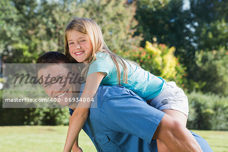 Daughter getting piggy back from dad in a park smiling at camera Stock Photo - Budget Royalty-Free, Image code: 400-06934004