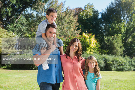 Cute family smiling at camera in the park on a sunny day Stock Photo - Budget Royalty-Free, Image code: 400-06934007