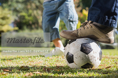 Child kicking the ball from fathers foot in the park Stock Photo - Budget Royalty-Free, Image code: 400-06934012