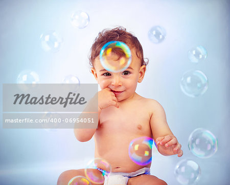 Photo of adorable baby boy isolated on blue background, sweet child sitting and playing with soap bubbles, cute kid bathing with soap-bubbles, portrait of smiling toddler in diaper Stock Photo - Budget Royalty-Free, Image code: 400-06954051
