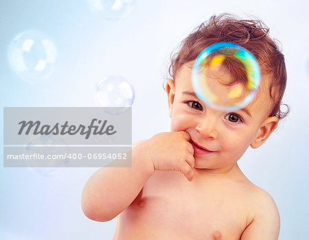Closeup portrait of naked nice toddler isolated on blue background, cute happy baby boy bathe, adorable child sitting with finger in mouth, infant play with soap-bubbles, healthy childhood Stock Photo - Budget Royalty-Free, Image code: 400-06954052