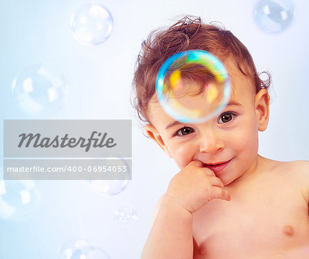 Closeup portrait of naked nice little kid isolated on blue background, cute happy baby boy bathe, adorable child with finger in mouth, sweet infant play with soap-bubble, healthy childhood Stock Photo - Budget Royalty-Free, Image code: 400-06954053