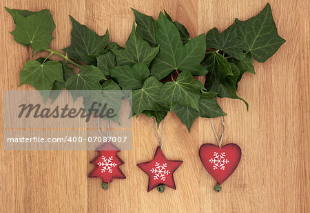 Old wooden christmas decorations hanging from ivy leaf sprigs over oak background. Stock Photo - Budget Royalty-Free, Image code: 400-07087007