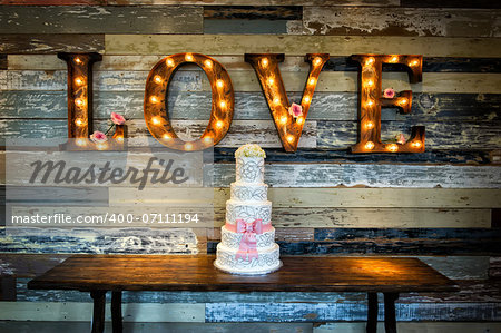 Image of a wedding cake with the word love as sinage on a rustic background Stock Photo - Budget Royalty-Free, Image code: 400-07111194