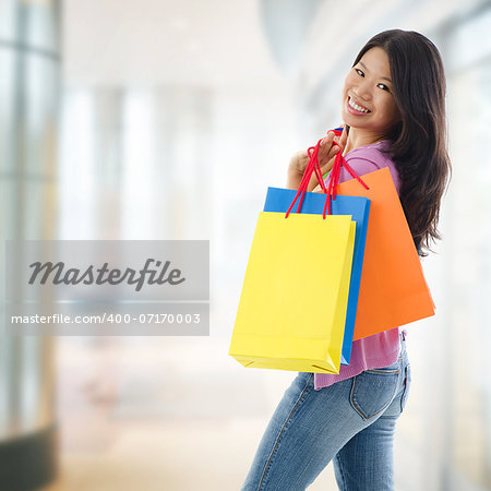 Happy Asian shopping woman smiling holding many shopping bags at the mall. Casual Asian shopper girl standing in department store. Beautiful mixed race Southeast Asian woman model. Stock Photo - Budget Royalty-Free, Image code: 400-07170003