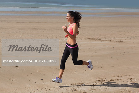 Full length of a healthy young woman jogging on shore at beach Stock Photo - Budget Royalty-Free, Image code: 400-07180892