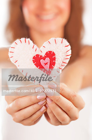 Picture of a small white heart in hands, female holds handmade sewn soft toy, macro, shallow dof, woman with Valentine gift, happy girl smiling, conceptual image of health care or love Stock Photo - Budget Royalty-Free, Image code: 400-07272531
