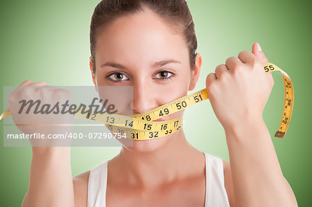 Woman with a yellow measuring tape around her mouth, in a green background Stock Photo - Budget Royalty-Free, Image code: 400-07290754