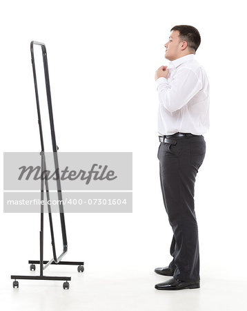 Overweight man admiring himself in a standing mirror as he checks the fit of his clothing and his appearance while dressing in the morning Stock Photo - Budget Royalty-Free, Image code: 400-07301604
