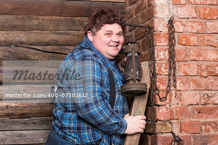 Happy overweight young man standing against a brick wall at the top of a stepladder laughing Stock Photo - Budget Royalty-Free, Image code: 400-07301612