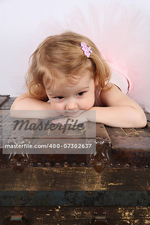 Little ballet girl wearing a pink tutu on an antique trunk Stock Photo - Budget Royalty-Free, Image code: 400-07302637