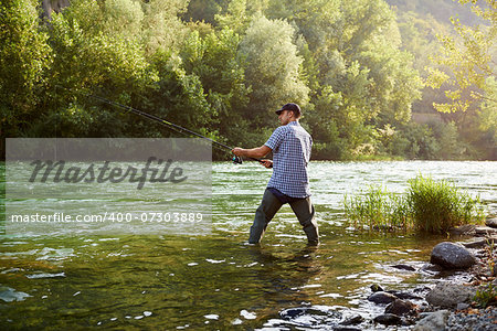 mid adult man on holidays on river, relaxing and fishing trout Stock Photo - Budget Royalty-Free, Image code: 400-07303889