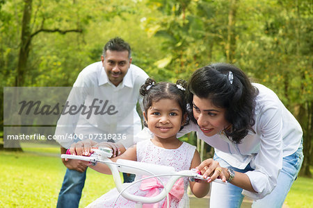Indian family outdoor activity. Asian parent teaching child to ride a bike at the park in the morning. Stock Photo - Budget Royalty-Free, Image code: 400-07318236