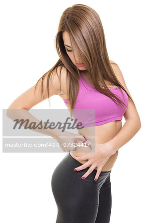 Beautiful fit young Caucasian woman looking down pinching fat on her waist wearing short purple shirt isolated on white background. Fitness and dieting concept. Stock Photo - Budget Royalty-Free, Image code: 400-07324417