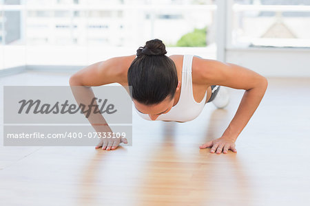 Determined beautiful young woman doing push ups in the gym Stock Photo - Budget Royalty-Free, Image code: 400-07333109