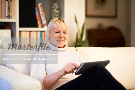 portrait of beautiful old woman using tablet pc and smiling, sitting on sofa at home Stock Photo - Budget Royalty-Free, Image code: 400-07445657