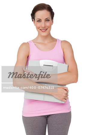 Portrait of a smiling young woman with weight scale over white background Stock Photo - Budget Royalty-Free, Image code: 400-07476315