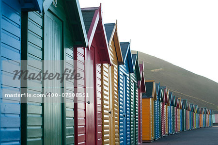 Row of colorful wooden beach huts overlooking Whitby Sands in North Yorkshire looking along the front facades of the receding line of huts Stock Photo - Budget Royalty-Free, Image code: 400-07508551