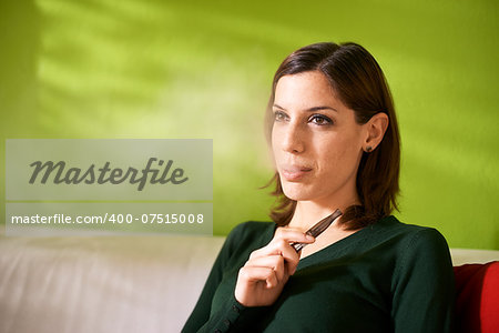 young female smoker smoking e-cigarette at home, sitting on sofa and relaxing Stock Photo - Budget Royalty-Free, Image code: 400-07515008