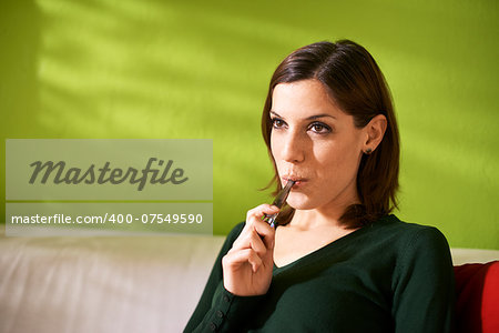 young female smoker smoking e-cigarette at home, sitting on sofa and relaxing Stock Photo - Budget Royalty-Free, Image code: 400-07549590
