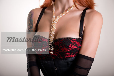 Busty redhead woman in vintage red bra, sheer gloves and pearl necklace Stock Photo - Budget Royalty-Free, Image code: 400-07549730