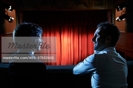 Arts and entertainment in theatre, with man and woman looking at stage with red curtains Stock Photo - Budget Royalty-Free, Image code: 400-07553615