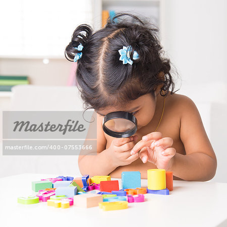 A little Indian girl zoom into toys through a magnifying glass, living lifestyle at home. Stock Photo - Budget Royalty-Free, Image code: 400-07553666