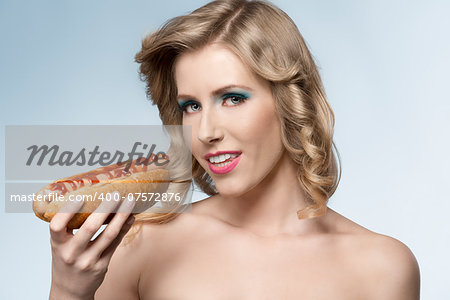 close-up portrait of sensual blonde female with fashion style, cute make-up and curly blonde hair-style posing with hot-dog in the hand Stock Photo - Budget Royalty-Free, Image code: 400-07572876