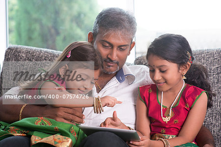 Indian family at home. Asian father and children using digital tablet computer, sitting on sofa, home schooling concept. Stock Photo - Budget Royalty-Free, Image code: 400-07574726