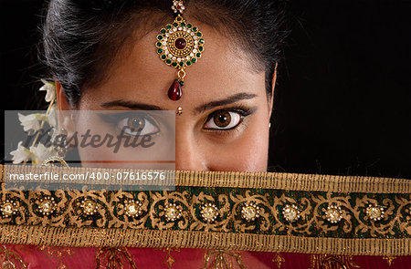 Portrait of beautiful mystery young Indian girl covering her face by veil, looking at camera, isolated on black background. Stock Photo - Budget Royalty-Free, Image code: 400-07616576