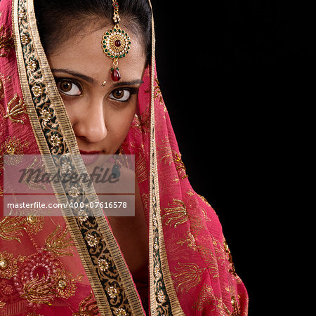 Portrait of beautiful mystery young Indian woman covering her face by headscarf, looking at camera, copy space at side, isolated on black background. Stock Photo - Budget Royalty-Free, Image code: 400-07616578