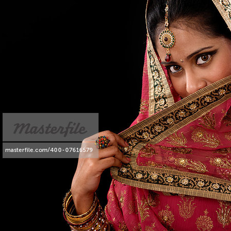 Portrait of beautiful mystery young Indian woman covering her face by veil, looking at camera, copy space at side, isolated on black background. Stock Photo - Budget Royalty-Free, Image code: 400-07616579