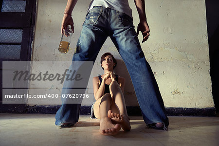 People, substance abuse and domestic violence. Drunk man standing with whiskey bottle and threatening his young wife at home Stock Photo - Budget Royalty-Free, Image code: 400-07620796