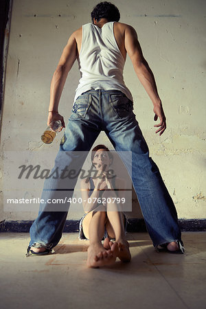 People, substance abuse and domestic violence. Drunk man standing with whiskey bottle and threatening his young wife at home Stock Photo - Budget Royalty-Free, Image code: 400-07620799