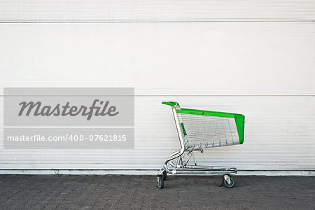Empty Shopping Cart parked in front of large supermarket. Consumerism concept. Stock Photo - Budget Royalty-Free, Image code: 400-07621815