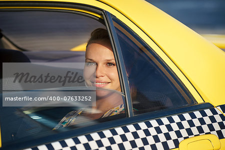 blond woman in yellow taxi looking out of car window and smiling. Tourism and business travel Stock Photo - Budget Royalty-Free, Image code: 400-07633252