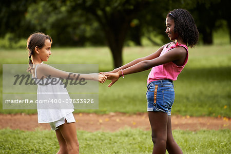 Two hispanic and african little girls playing ring around the rosie in public park and holding hands Stock Photo - Budget Royalty-Free, Image code: 400-07633926