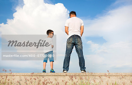 father and son standing on a stone platform and pee together Stock Photo - Budget Royalty-Free, Image code: 400-07720000