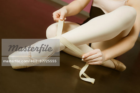 Ballerina tying the ribbon on her ballet slippers in the ballet studio Stock Photo - Budget Royalty-Free, Image code: 400-07725555