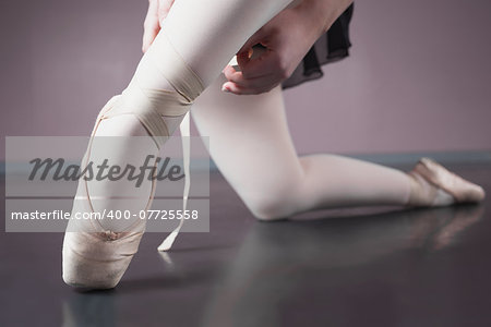 Ballerina tying the ribbon on her ballet slippers in the ballet studio Stock Photo - Budget Royalty-Free, Image code: 400-07725558