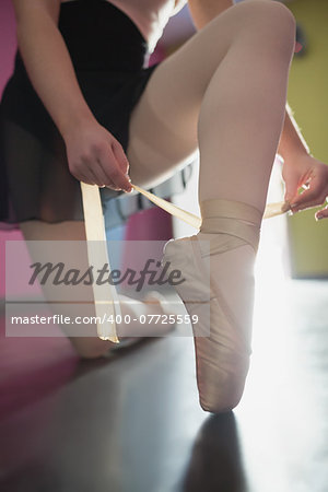 Ballerina tying the ribbon on her ballet slippers in the ballet studio Stock Photo - Budget Royalty-Free, Image code: 400-07725559